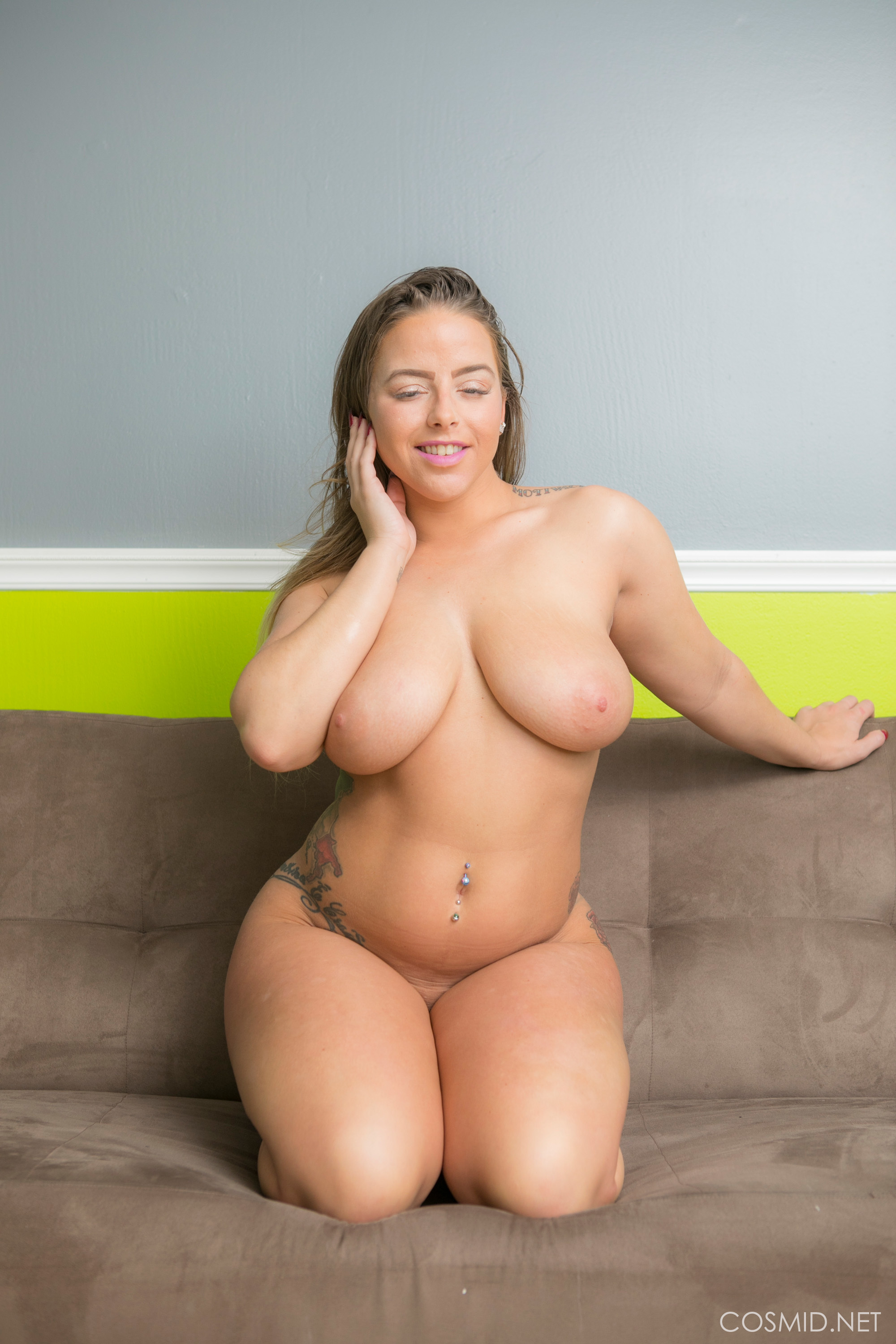 Chubby brunette with tattoos shows off her big tits at ...