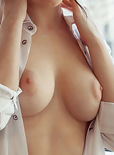Busty brunette shows off her shaved pussy