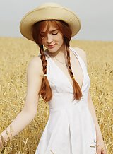 Redhead with pale skin spreading in a field
