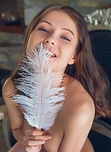 Beautiful brunette babe plays with feathers