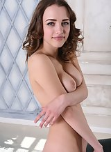 Shaved brunette with big tits posing nude