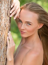 Freckled blue-eyed girl nude by a tree