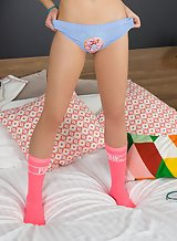 Cute teen in pink socks spreading in bed