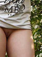 Shaved blonde teen nude in a field
