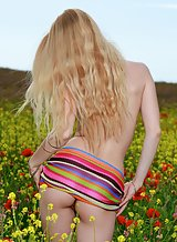 Shaved blonde with puffy nipples nude in a field
