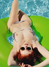 Freckled redhead nude in the pool