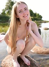 Cute blonde with pale skin nude in a lake