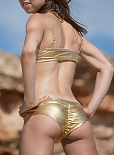 Athletic girl takes off her golden bikini