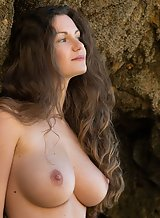 Busty brunette nude by the sea