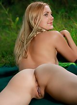 Blonde with tan lines nude in a field
