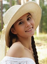 Cute brunette teen Leona Mia spreading in a field