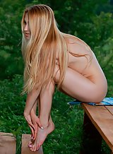 Flat-chested blonde with puffy nipples spreading on a table