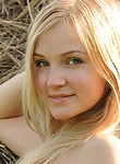 Lovely blonde teen nude by a haystack