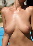 Busty brunette toying by the pool