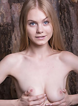 Busty blonde with pale skin nude in a forest