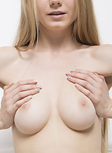 Busty blonde with pale skin posing nude