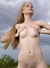 Busty blonde with pale skin nude in a field