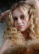 Curly-haired blonde with pale skin posing nude