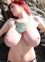 Busty petite redhead nude by some rocks