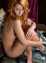 Tanned redhead spreads her bald pussy