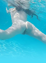 Brunette with pale skin masturbating in a pool