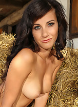 Gorgeous busty brunette nude in a haystack
