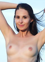 Shaved black-haired girl spreading in a field