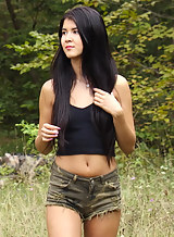 Black-haired teen toying on some rocks