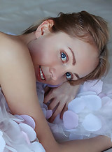 Blue-eyed blonde with pale skin spreading in bed