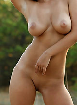 Busty redhead with tan lines nude in a field