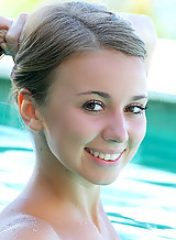 Cute blonde teen nude in a pool