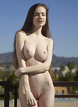 Long haired Emily Bloom displays her pale nude body and big tits outdoors