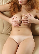 Shaved redhead with saggy tits spreads her shaved pussy