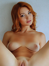 Busty redhead with tan lines posing nude