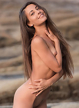 Long-haired brunette with small tits nude by the sea