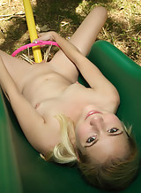 Petite blonde cutie spreads her bald pussy in a park