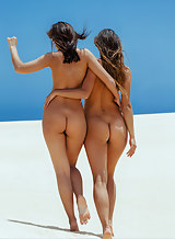 Brunette lesbians nude in the sand