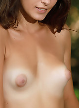 Brunette with puffy nipples and tan lines nude by a creek