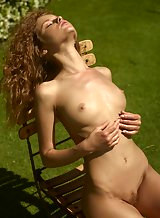 Redhead babe Julia sunbathes nude to flaunt her tight body