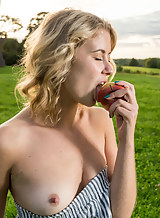 Shaved blonde with tan lines nude in a field